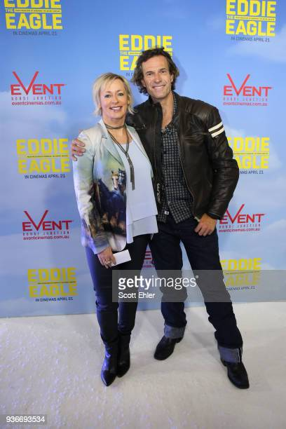 AMANDA KELLER AND BRENDAN JONES POSE BY MEDIA WALL AT THE EDDIE THE EAGLE PREMIERE IN SYDNEY SMILING