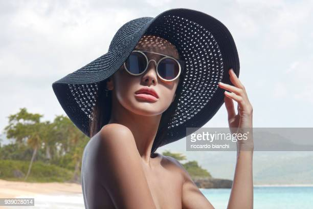 POSH BRUNETTE GIRL WEARING A BLACK SUMMER HAT AND SUNGLASSES