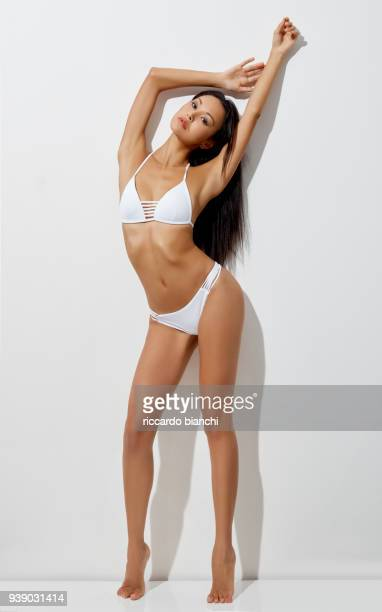 asian brunette girl wearing a white bikini under sunlight - asian swimsuit models stock photos and pictures