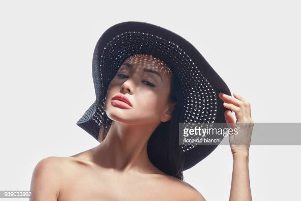 posh brunette girl wearing a black summer hat - big lips stock photos and pictures