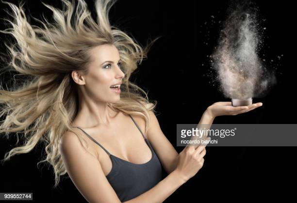 BLONDE WOMAN HOLDING POWDER MAKE-UP WHILE EXPLODING