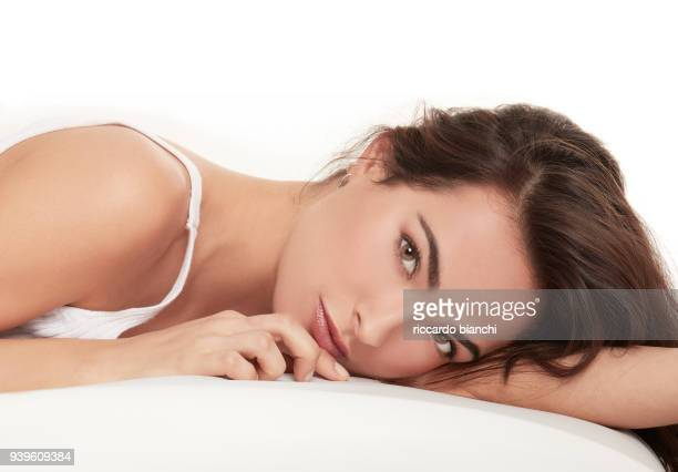 BRUNETTE WOMAN WITH NATURAL LOOK LAYING IN BED