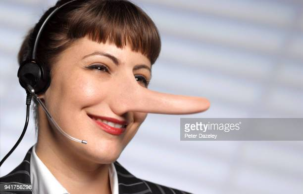 customer care - call centre woman telling lies - long nose stock photos and pictures