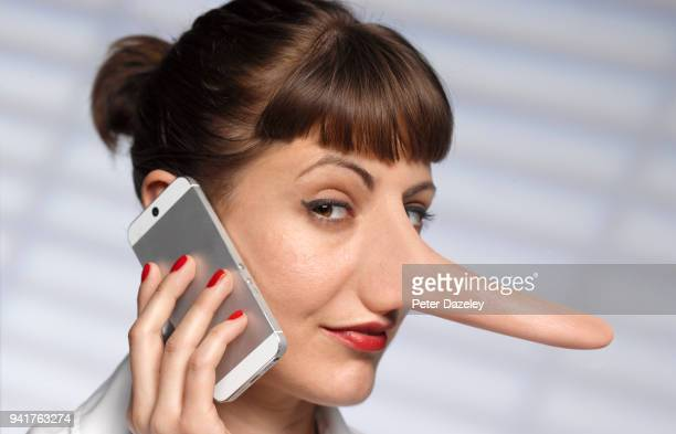 woman telling lies  on mobile phone - gossip stock pictures, royalty-free photos & images