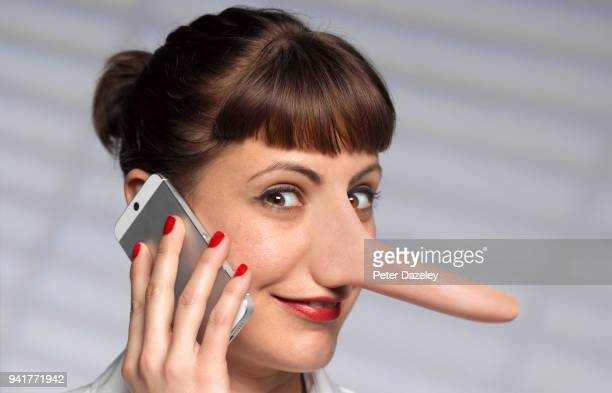 woman spreading rumours on mobile phone - long nose stock photos and pictures
