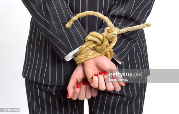 business woman with hands tied behind back - control stock pictures, royalty-free photos & images