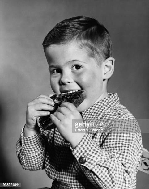 PORTRAIT OF BOY EATING BREAD WITH JAM