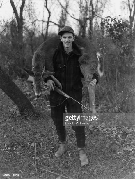 YOUNG MALE HUNTER CARRYING DEAD DEER