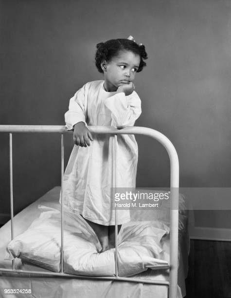 YOUNG GIRL STANDING ON HOSPITAL BED