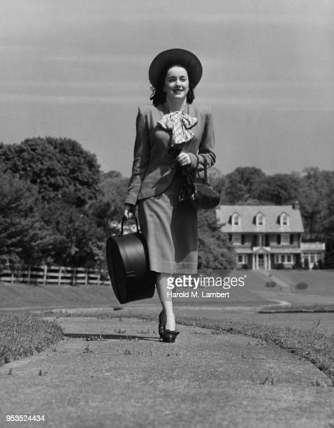 MID ADULT WOMAN WALKING WITH HAT CASE
