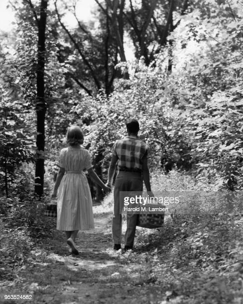 COUPLE WALKING THROUGH FOREST WITH PICNIC BASKET
