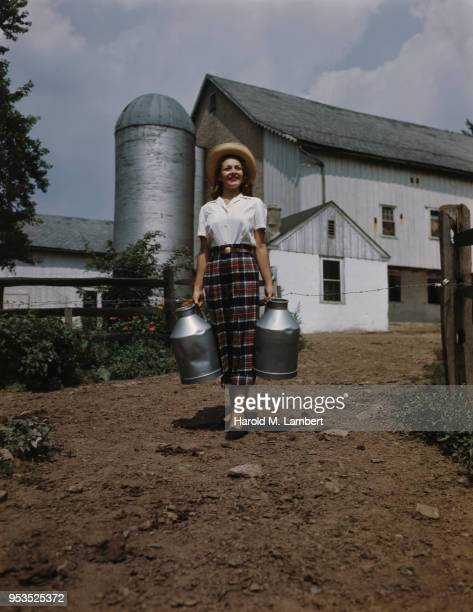 woman holding milk churn and walking - milk maid stock photos and pictures