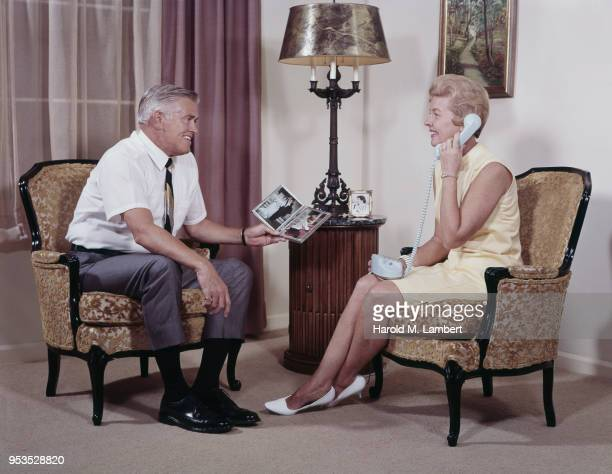 MATURE COUPLE IN LIVING ROOM, WOMEN TALKING ON TELEPHONE AND MEN HOLDING PICTURE FRAME