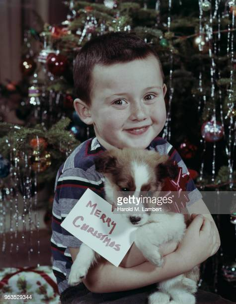 PORTRAIT OF BOY HOLDING DOG WITH CHRISTMAS CARD