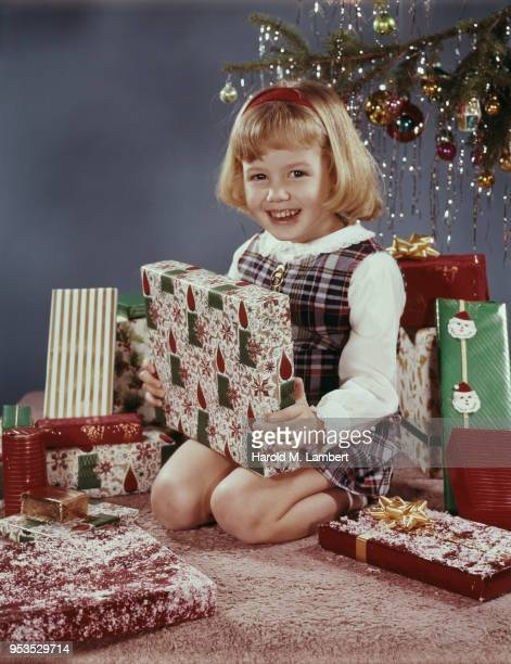 PORTRAIT OF GIRL WITH CHRISTMAS GIFTS, SMILING