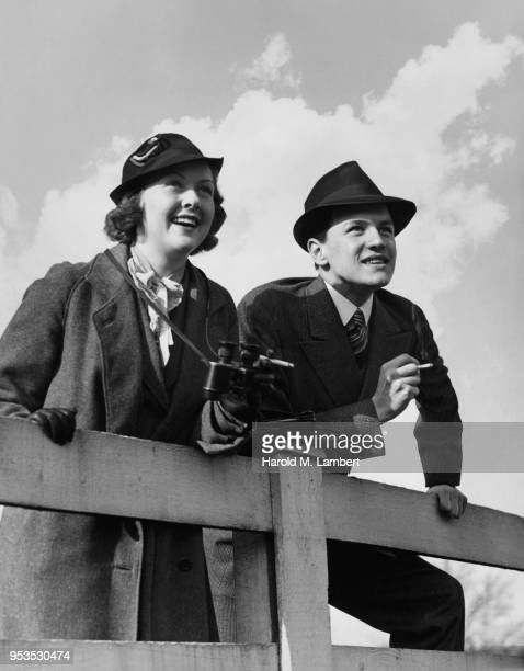 YOUNG COUPLE STANDING NEXT TO FENCE