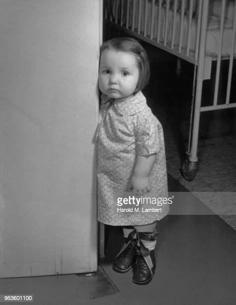 PORTRAIT OF GIRL STANDING AT DOOR IN HOSPITAL