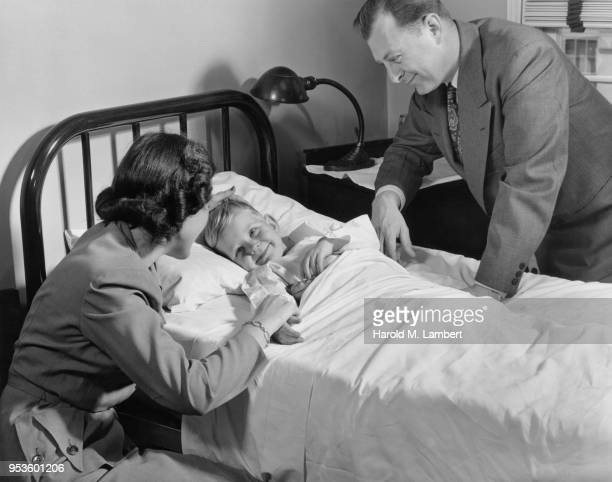 MOTHER AND FATHER CONSOLING TO THEIR SON IN HOSPITAL
