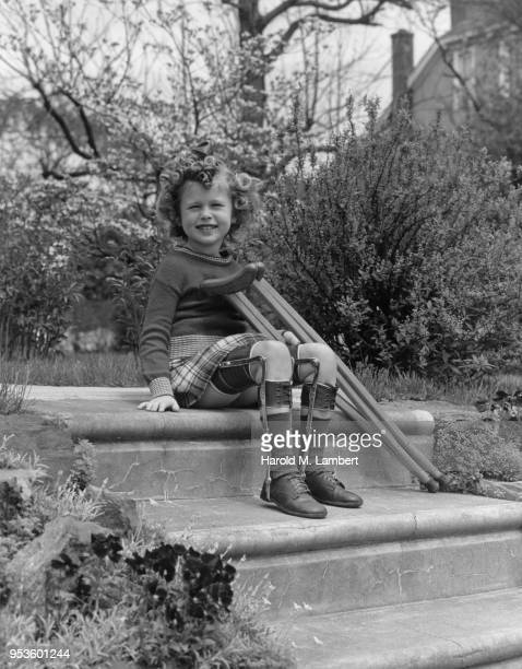 PORTRAIT OF GIRL SITTING ON STEPS WEARING LEG BRACES AND HOLDING CRUTCHES