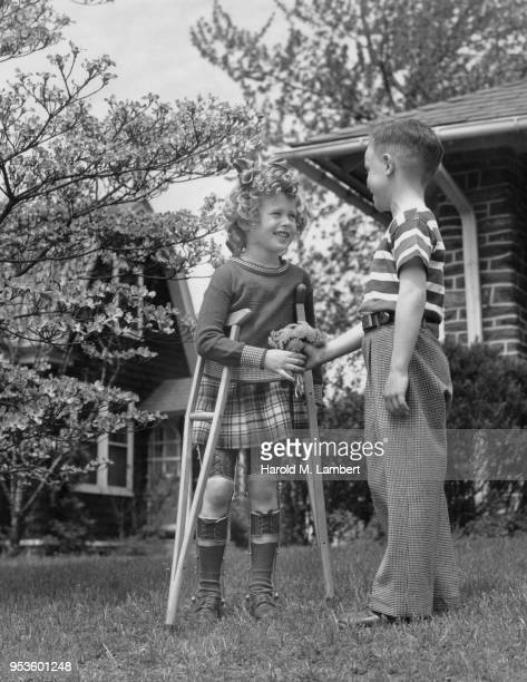 BOY GIVING BUNCH OF FLOWERS TO GIRL ON CRUTCHES
