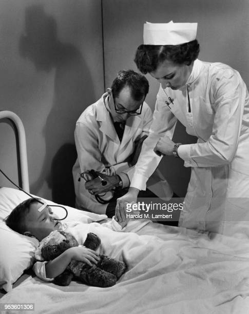 FEMALE NURSE CHECKING PULSE OF BOY WHILE DOCTOR IS SITTING BESIDE