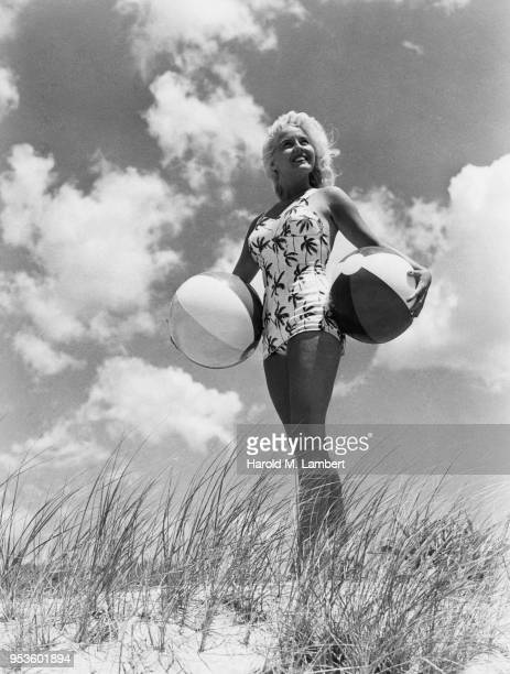 YOUNG WOMAN HOLDING TWO BEACH BALLS
