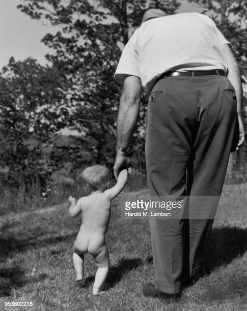 BABY BOY WALKING WITH FATHER IN PARK