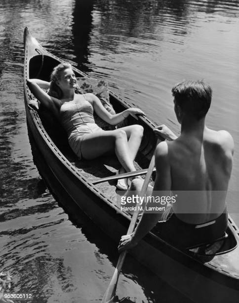 YOUNG MAN AND YOUNG WOMAN RIDING IN A CANOE