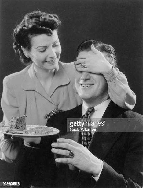 MID ADULT WOMAN COVERING EYES OF MATURE MAN WHILE HOLDING FOOD