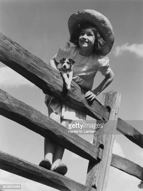 GIRL AND PUPPY STANDING ON FENCE