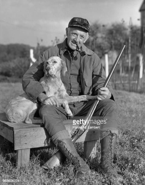 SENIOR MALE HUNTER SITTING WITH HIS DOG AND SMOKING HIS PIPE