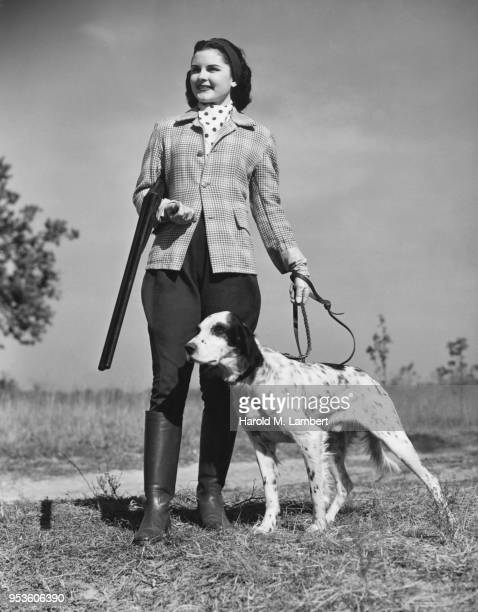 YOUNG WOMAN HUNTER AND HER DOG WAITING FOR HER CATCH IN FIELD