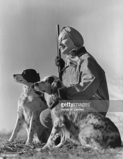 YOUNG FEMALE HUNTER HOLDING HER RIFLE AND SITTING WITH DOGS