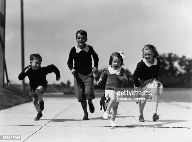 CHILDREN RUNNING ON PAVEMENT ROAD WITH DOG