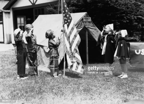 boys in military uniform and girls in nurse costume while hoisting flag - escrita ocidental - fotografias e filmes do acervo