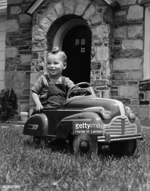 BOY SITTING IN TOY PEDAL CAR