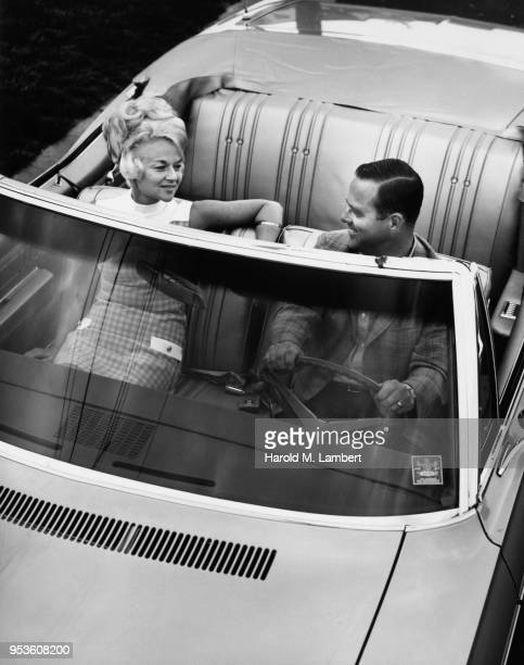 COUPLE LOOKING AT EACH OTHER WHILE SITTING IN CONVERTIBLE CAR