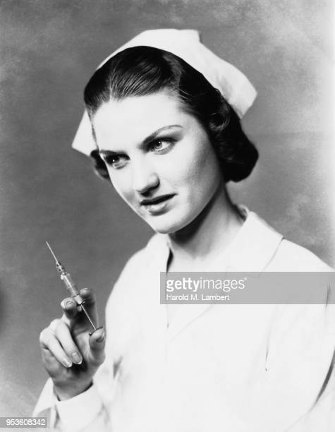 mid adult nurse preparing injection - historisch stock-fotos und bilder