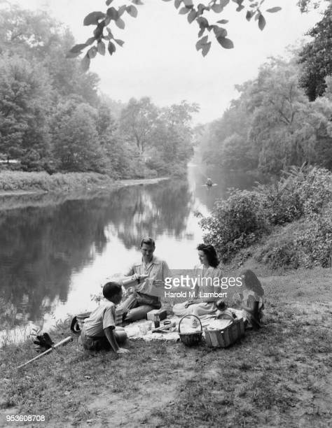 FAMILY HAVING PICNIC AT RIVERSIDE
