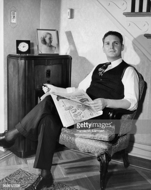 MID ADULT MAN READING NEWSPAPER AND LISTENING TO RADIO