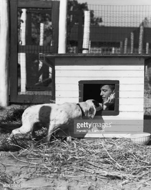 MID ADULT MAN IN KENNEL WITH DOG STANDING OUTSIDE