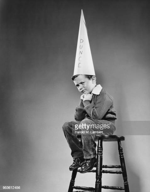 SCHOOLBOY SITTING ON STOOL WITH DUNCE HAT