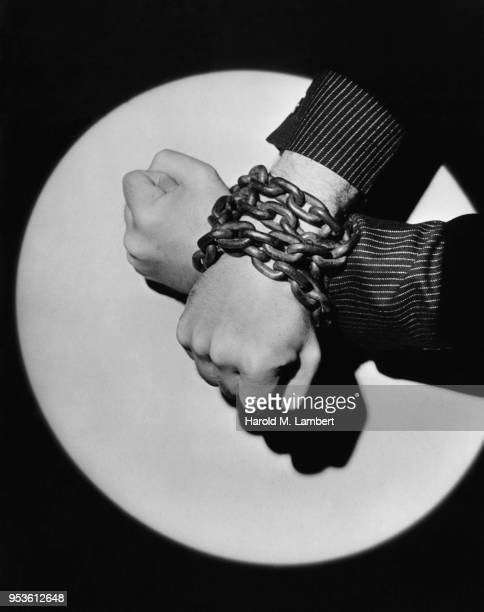 CLOSE-UP OF HANDS BOUND IN HEAVY METAL CHAINS