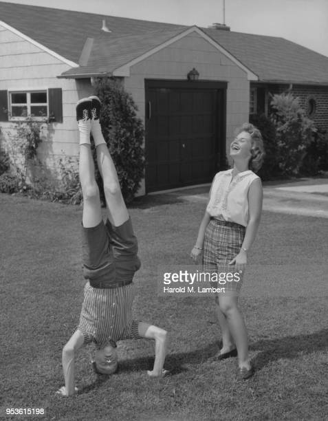 YOUNG MAN IN HEADSTAND POSITION WITH WOMAN LOOKING AT HIM
