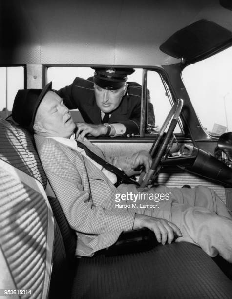 LAW ENFORCEMENT OFFICER LOOKING DRUNK MALE SITTING IN CAR