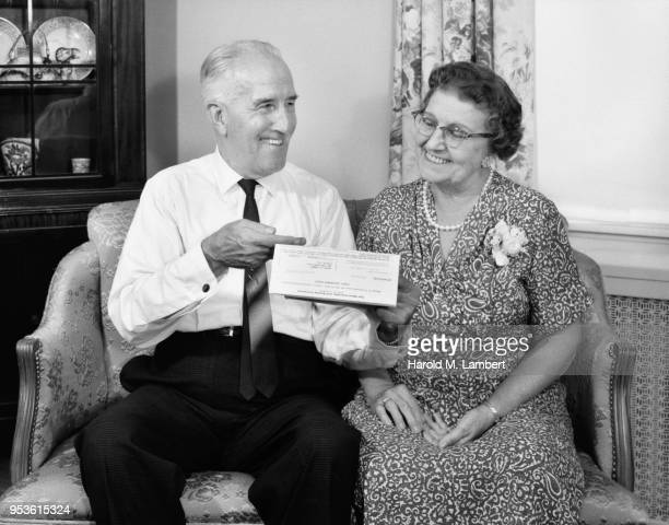 senior couple smiling while reading bill in living room - neckwear stock pictures, royalty-free photos & images
