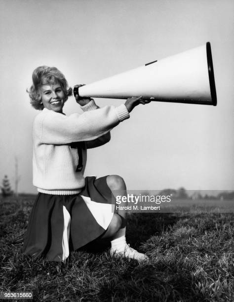 PORTRAIT OF FEMALE CHEERLEADER HOLDING MEGAPHONE