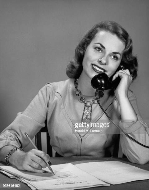 PORTRAIT OF BUSINESSWOMAN WRITING NOTES WHILE TALKING ON TELEPHONE