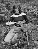 teenage girl feeding fawn