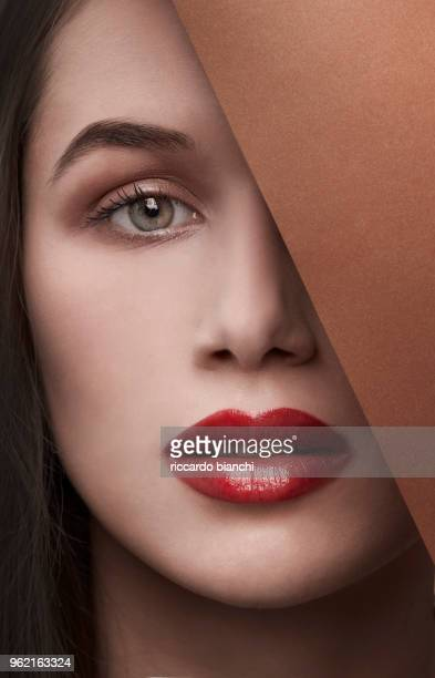 brunette woman with red lips behind a brown corner - matte lips stock pictures, royalty-free photos & images